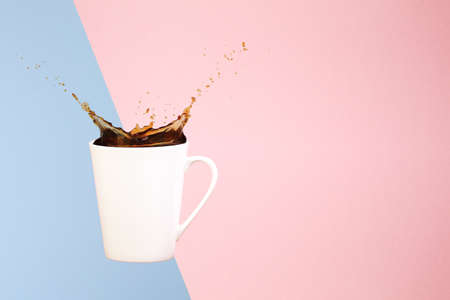 Coffee concept. Minimal art. Solid background. Coffee splashes. Levitating mug. Pink and light blue background. Horizontal, straight cup