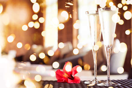 Two glasses of champagne with red flower in a spa lounge. Spa time concept. Spa lounge area. Valentines background. Romance concept. Horizontal, bold festive bokeh Standard-Bild - 116997522