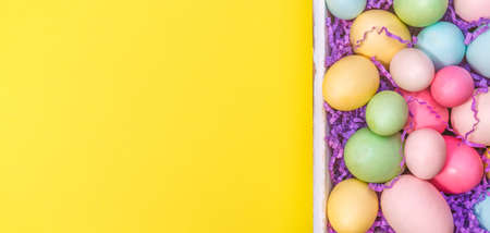 Multicolor eggs in a white tray. Creative Easter concept. Modern solid yellow background. Horizontal, wide screen banner Standard-Bild - 120552863