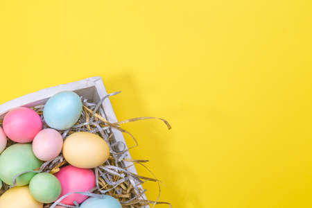 Multicolor eggs in a white tray. Creative Easter concept. Modern solid yellow background. Standard-Bild - 120552865