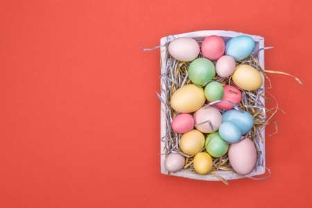 Multicolor eggs in a white tray. Creative Easter concept. Modern solid living coral background.  Color of the year inspired. Horizontal Standard-Bild - 120552867