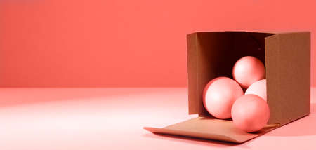 Eggs falling out of the craft cardboard box. Creative Easter concept. Modern solid background. Horizontal, wide screen banner. Living coral accent, color of the year 2019 Standard-Bild - 120552870