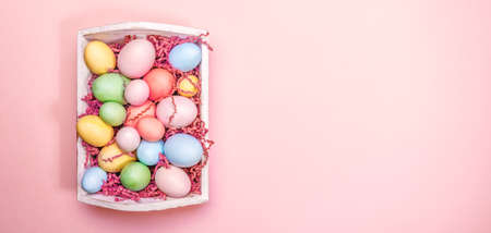 Multicolor eggs in a white tray. Creative Easter concept. Modern solid pink background. Horizontal, wide screen banner. Living coral accent, color of the year 2019 Standard-Bild - 120552869