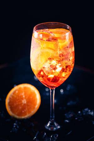 Stylish alcoholic aperol spritz trendy cocktail with orange slice on black background. Vertical Standard-Bild - 120552876