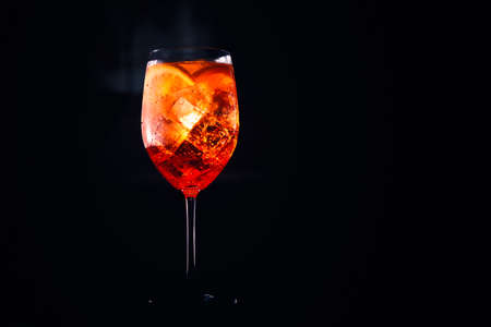 Tasty alcoholic aperol spritz trendy cocktail with orange slice on black background. Place for text. Standard-Bild - 120552875