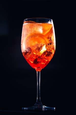 Stylish alcoholic aperol spritz trendy cocktail with orange slice on black background. Champagne cocktail. Standard-Bild - 120552877