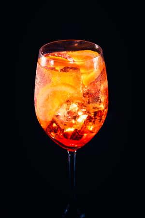 Stylish alcoholic aperol spritz trendy cocktail with orange slice on black background. Vertical photo. Standard-Bild - 120552880