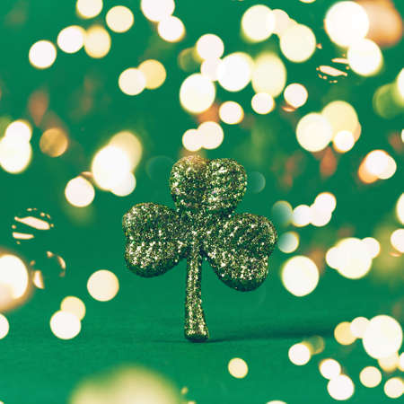 Glitter shamrock on green paper background. St Patricks day symbol. Irish National holiday concept. Square. Bold festive bokeh Standard-Bild - 120552879