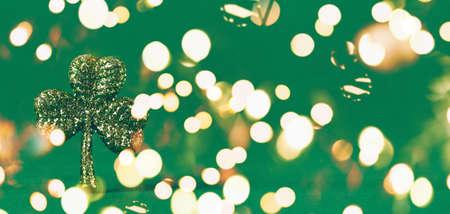 Trébol de brillo sobre fondo de papel verde. Símbolo del día de San Patricio. Concepto de fiesta nacional irlandesa. Formato de banner de pantalla ancha horizontal. Bokeh festivo audaz