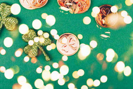 Glitter shamrocks and golden coins on green paper background. St Patricks day symbol. Irish National holiday concept. Horizontal. Bold festive bokeh Standard-Bild - 120552883