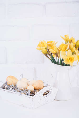 Jar with narcissuses and eggs at the white brick background. Spring and Easter concept. Vertical Standard-Bild - 120552899