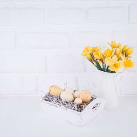 Jar with narcissuses and eggs at the white brick background. Spring and Easter concept. Square Standard-Bild - 120552901