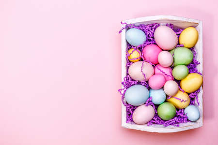 Multicolor eggs in a white tray. Creative Easter concept. Modern solid pink background. Standard-Bild - 120552902