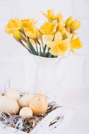 Jar with narcissuses and eggs at the white brick background. Spring and Easter concept. Vertical Standard-Bild - 120552903