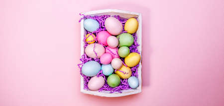 Multicolor eggs in a white tray. Creative Easter concept. Modern solid pink background. Banco de Imagens