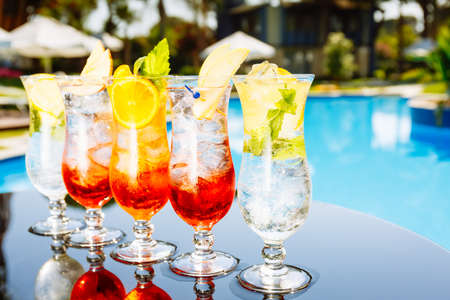 Craft cocktails near the pool. Vacation, summer, holiday, luxury resort concept. Horizontal