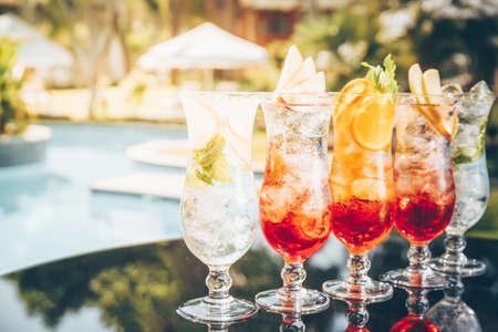Craft cocktails near the pool. Vacation, summer, holiday, luxury resort concept. Horizontal, toned image, sunset warm hue Standard-Bild - 120552939
