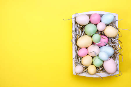 Multicolor eggs in a white tray. Creative Easter concept. Modern solid yellow background. Horizontal Standard-Bild - 120552943