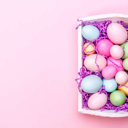 Multicolor eggs in a white tray. Creative Easter concept. Modern solid pink background. Square Standard-Bild - 120552946