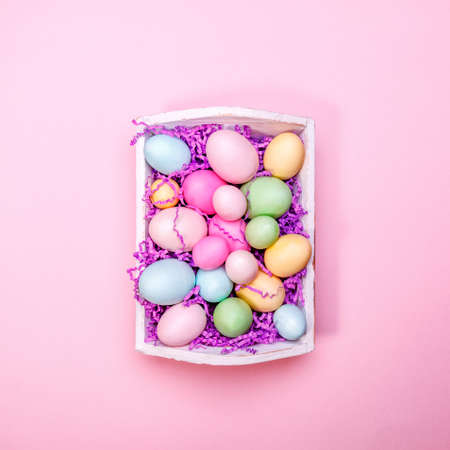 Multicolor eggs in a white tray. Creative Easter concept. Modern solid pink background. Square Standard-Bild - 120552949