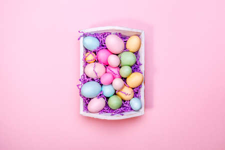 Multicolor eggs in a white tray. Creative Easter concept. Modern solid pink background. Standard-Bild - 122380217
