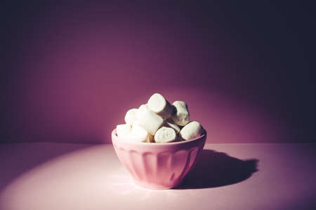 Pink bowl of giant marshmallows on pink backdrop with harsh shadows Standard-Bild - 122380220