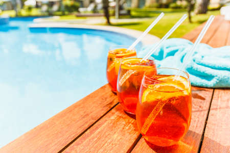 Three glasses of aperol spritz and negroni cold cocktail on wooden edge of swimming pool with turquoise towel. Vacation concept. Place for text. Standard-Bild - 122380224