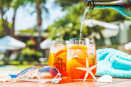 Barman is pouring aperol spritz cocktail into one of two glasses with orange slices. Some seashells, towel and sunglasses closed to swimming pool. Vacation concept. Standard-Bild - 122380226