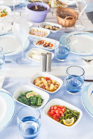 Varioius meze starters in an outdoor greek restaurant. Healthy vegetarian snacks. Local mediterranean cuisine Standard-Bild - 122380233