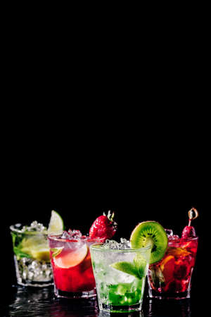 Four colorful tasty alcoholic cocktails in a row at the bar stand. Luxury vacation concept. Place for text. Vertical, isolated on black Standard-Bild - 122380239