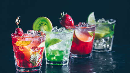 Four colorful tasty alcoholic cocktails in a row at the bar stand. Luxury vacation concept. Place for text. Banner wide screen format Standard-Bild - 122380241