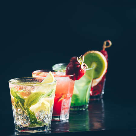 Four colorful tasty alcoholic cocktails in a row at the bar stand. Luxury vacation concept. Place for text. Standard-Bild - 122380306