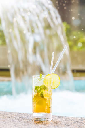 Glass of classic mojito cocktail with caipirinha on stone edge of swimming pool with waterfall background. Luxury vacation concept. Close up. Standard-Bild - 122380317