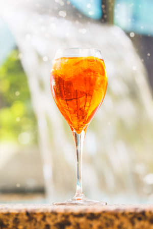 Glass of aperol spritz and negroni cocktail on stone edge of swimming pool with waterfall background. Luxury vacation concept. Close up. Standard-Bild - 122380318
