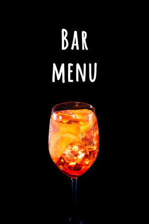 Stylish alcoholic trendy cocktail with orange slice on black background. Vertical photo.. Bar menu wording Imagens