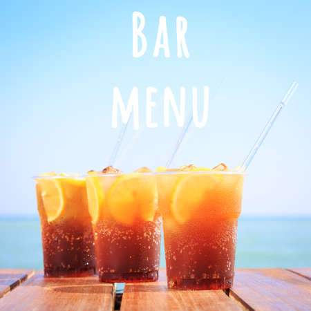 Concept of luxury tropical vacation. Cuba Libre or long island iced tea cocktail on the pier. Beach party. Clear blue sky. Square. Bar menu wording Zdjęcie Seryjne