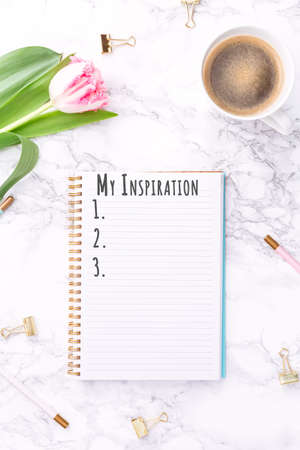 Pink tulips with festive stationary and coffee on white marble background. My Inspiration wording. Copy space Top view. Vertical