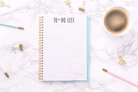 Festive golden stationary and coffee on white marble background. To-do list wording. Copy space. Top view. Horizontal