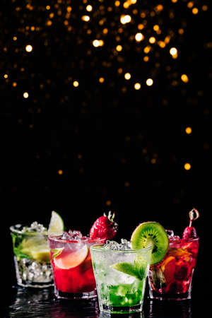 Four colorful tasty alcoholic cocktails in a row at the bar stand. Luxury vacation concept. Place for text. Vertical. Festive holiday bokeh Imagens