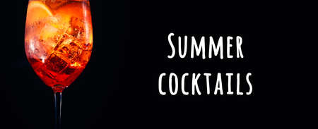 Tasty alcoholic trendy cocktail with orange slice on black background. Macro, wide screen banner format. Summer cocktails wording