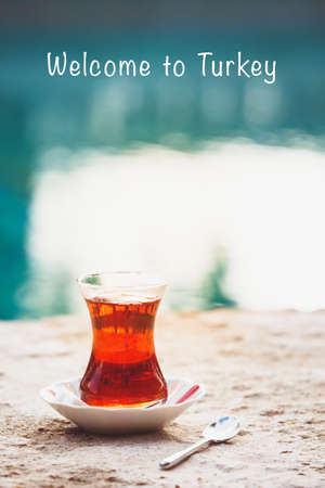 Hot turkish tea outdoors near water. Turkish tea and traditional turkish culture concept. Vertical. Toned image. Welcome to Turkey text Imagens