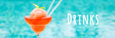 Frozen strawberry margarita cocktail near the resort outdoor pool. Concept of luxury vacation. Horizontal, wide screen banner format. Drinks wording