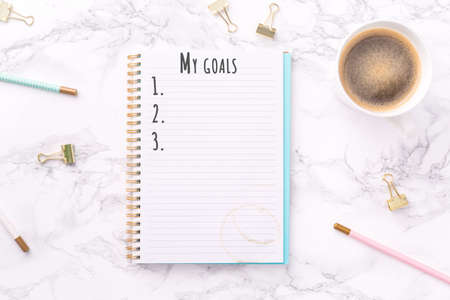 Festive golden stationary and coffee on white marble background. My Goals wording. Copy space. Top view. Horizontal