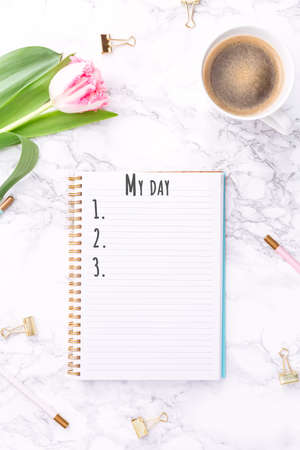 Pink tulips with festive stationary and coffee on white marble background. My day wording. Copy space Top view. Vertical
