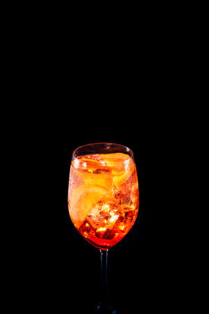 Stylish alcoholic trendy cocktail with orange slice on black background. Place for your text. Vertical photo.