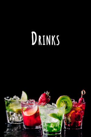 Four colorful tasty alcoholic cocktails in row at the bar stand. Luxury vacation concept. Place for text. Vertical, isolated on black. Drinks wording Imagens - 126501073