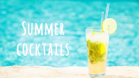 Mojito cocktail at the edge of an outdoor resort pool. Concept of luxury vacation. Horizontal, wide screen format. Summer cocktails wording Imagens