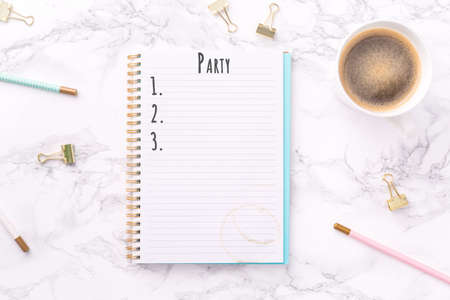 Festive golden stationary and coffee on white marble background. Party wording. Copy space. Top view. Horizontal