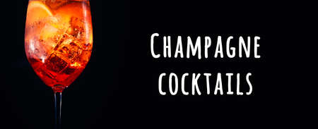 Tasty alcoholic trendy cocktail with orange slice on black background. Macro, wide screen banner format. Champagne cocktails wording