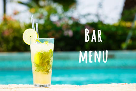 Mojito cocktail at the edge of a resort pool. Concept of luxury vacation. Outdoor pool background. Horizontal. Bar menu wording